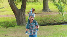 Father and son having fun in the park stock footage