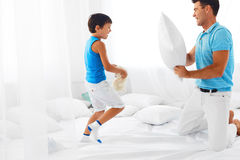 Father and son having fun. Pillow fight. Dad and son having fun . Pillow fight in the bed at home. Happy parenthood and carefree childhood Royalty Free Stock Image