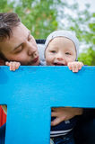 Father and son having fun in playground. Father with son having fun in playground. Smiling father and baby boy on playground. Father and son hugging and playing royalty free stock photo
