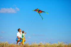 Father and son having fun, playing with kite together Royalty Free Stock Image