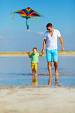 Father and son having fun, playing with kite together Royalty Free Stock Photo