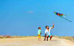 Father and son having fun, playing with kite together Royalty Free Stock Photography