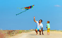 Father and son having fun, playing with kite together Royalty Free Stock Images
