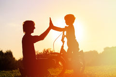 Father and son having fun riding bike at sunset. Active kids sport Royalty Free Stock Photos