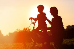 Father and son having fun riding bike at sunset. Active kids sport Royalty Free Stock Images