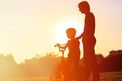 Father and son having fun riding bike at sunset Royalty Free Stock Photography
