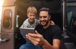 Father and son having fun on road trip with digital tablet Royalty Free Stock Photo
