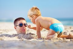 Father and son having fun in sand on the beach. Father and son having fun together in sand on the beach stock images