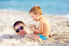 Father and son having fun in sand on the beach Stock Photography