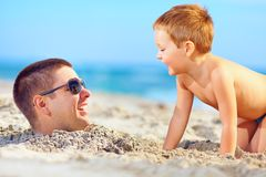 Father and son having fun in sand, laughing on the beach Stock Photos