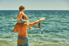 Father and son having fun at sea. Father and son on the beach. The son sits on the shoulders of his father royalty free stock photo