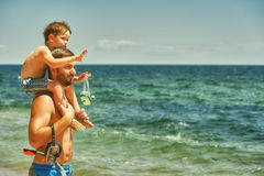 Father and son having fun at sea. Father and son on the beach. The son sits on the shoulders of his father royalty free stock photography