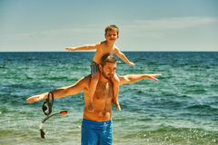 Father and son having fun at sea. Father and son on the beach. The son sits on the shoulders of his father royalty free stock image