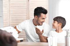 Father and son having fun while shaving. In bathroom royalty free stock photos