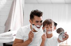 Father and son having fun while shaving. In bathroom royalty free stock photo