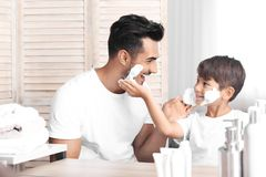 Father and son having fun while shaving. In bathroom stock images