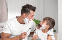 Father and son having fun while shaving. In bathroom stock photo