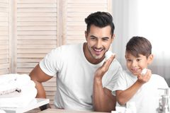 Father and son having fun while shaving. In bathroom royalty free stock photography