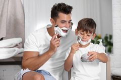 Father and son having fun while shaving. In bathroom stock photos