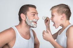 Father and son shaving together. Father and son having fun while shaving together isolated on grey Royalty Free Stock Photography