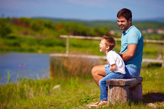 Father and son having fun, sitting on the bench by the lake on sunny summer day Stock Photos