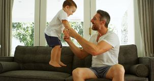 Father and son having fun on sofa 4k. Father and son having fun on sofa at home 4k stock footage