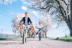 Father and son having fun spreading wide legs and screaming when riding bicycles on country road under blossom trees. Healthy royalty free stock images