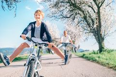 Father and son having fun spreading wide legs and screaming when riding bicycles on country road under blossom trees. Healthy stock photo