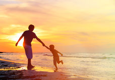 Father and son having fun on sunset beach Royalty Free Stock Photos