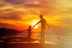 Father and son having fun on sunset beach Stock Image