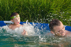 Father and son having fun in the swimming pool Royalty Free Stock Photo