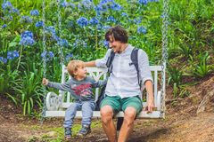 Father and son having fun on swings in a flower garden.  Royalty Free Stock Photos