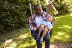 Father And Son Having Fun On Tire Swing In Garden Royalty Free Stock Photo