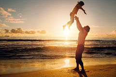 Father and son having fun together in sunset ocean Stock Photos