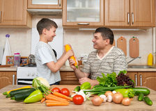 Father and son having fun with vegetables in home kitchen interi Stock Images