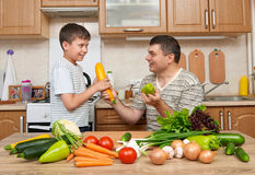 Father and son having fun with vegetables in home kitchen interi Royalty Free Stock Image