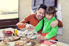 Father and son having lunch in a chalet Stock Photos