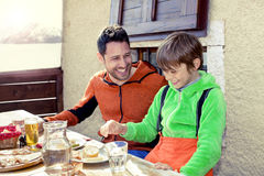 Father and son having lunch in a chalet Stock Photography