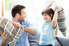 Father and son having pillow fight Stock Photography