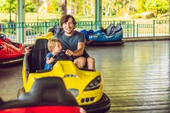 Father and son having a ride in the bumper car at the amusement park.  stock photo