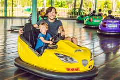 Father and son having a ride in the bumper car at the amusement park.  stock images