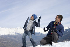Father and son (7-9) having snow ball fight in snow field, mountain range in background Royalty Free Stock Photo