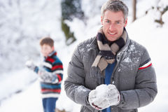 Father And Son Having Snowball Fight. In Winter Landscape stock image