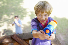 Father And Son Having Water Pistol Fight In Tree House Stock Photo