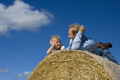 Father and son (7-9) on hay bale, smiling at each other, low angle view Royalty Free Stock Photo