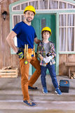 Father and son in helmets with building tools. Standing on porch Stock Photos