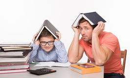 Father and son hiding under books Stock Images