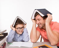 Father and son hiding under books Stock Photo