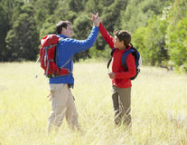 Father And Son On Hike In Beautiful Countryside Giving High Five Stock Image