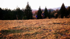 Father and son on a hike, top of the hill, autumn stock footage